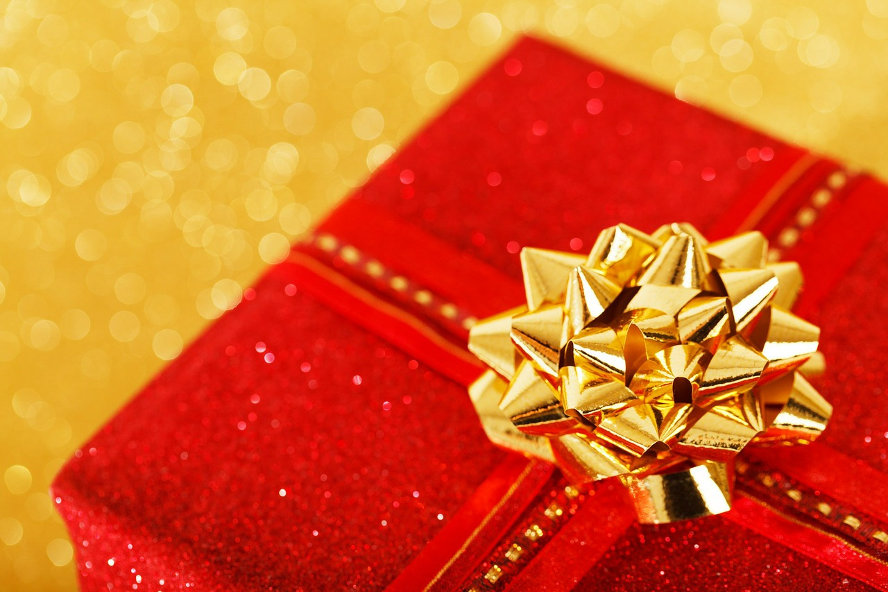 Picture of a red gift box wrapped with gold ribbon